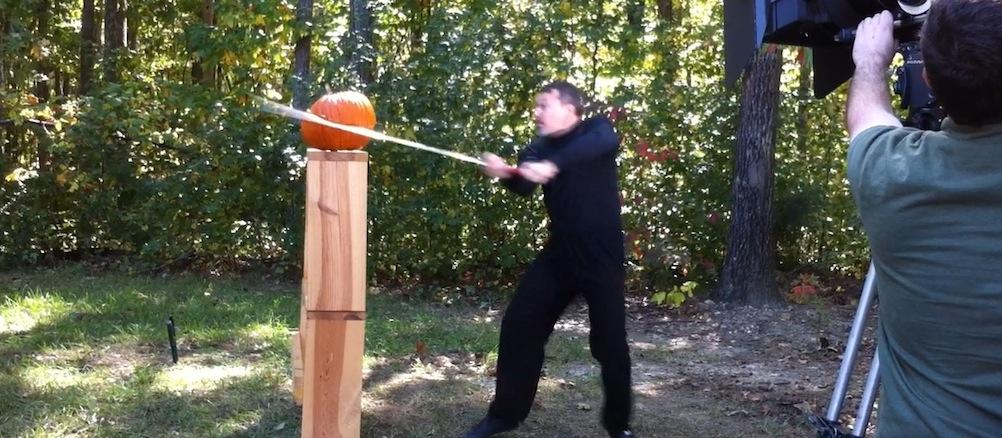 cutting a pumpkin with a medieval sword